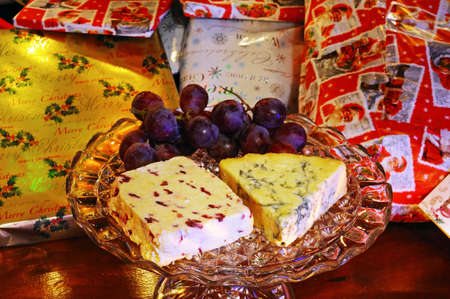 wensleydale: Wensleydale with cranberries and Blue Stilton cheeses with red grapes on a glass plate stand with Christmas presents to the rear, England, UK, Western Europe