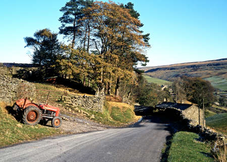 Tractor parked by a dry stone wall with a vie towards the village and farmhouses, Thwaite, Yorkshire Dales, North Yorkshire, England, UK, Great Britain, Western Europe