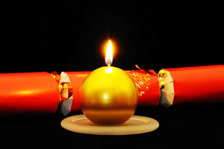 u k: Round gold Christmas candle with a red Christmas cracker set against a black , England, UK, Western Europe