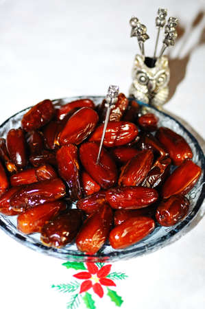 the novelty: Dates in a shallow glass dish novelty owl toothpicks pickle skewers, England, UK, Western Europe