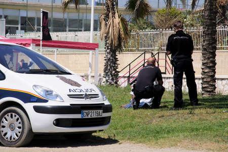 vagrant: Malaga, Spain - June 14, 2011 - Two police officers talking to a vagrant on the edge of Malagueta beach, Malaga, Costa del Sol, Malaga Province, Andalucia, Spain, Western Europe