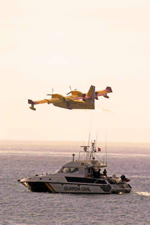 Calahonda, Spain - September 12, 2011 - Bombardier Canadair CL415 fire bomber  Number 2069-4333  flying over a Guardia Civil Boat after collecting seawater for fire fighting, Calahonda, Costa del Sol, Malaga Province, Andalucia, Spain, Western Europe