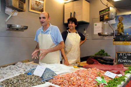 writing western: Malaga, Spain - June 14, 2011 - Fishmongers at fish stall in the indoor market  Mercado de Atarazanas , Malaga, Costa del Sol, Malaga Province, Andalusia, Spain, Western Europe  Editorial