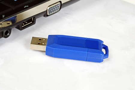 rewritable: Blue USB stick sitting alongside a netbook