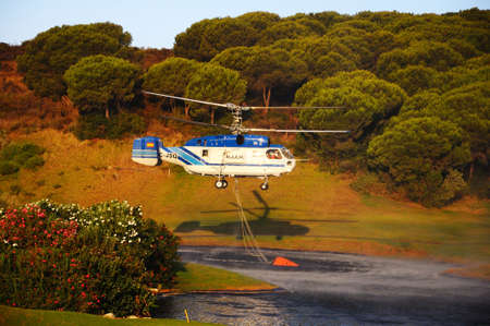 Cabopino Golf, Spain - September 12, 2011 - Kamov Ka-32A11BC helicopter  registration EC-JSQ  collecting water for fire fighting from a golf course lake, Cabopino Golf, Costa del Sol, Malaga Province, Andalucia, Spain, Western Europe