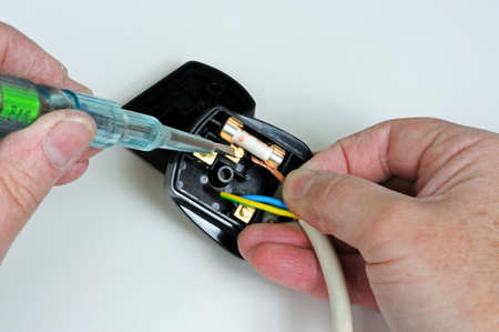 Man wiring English 3 pin 13 amp plug - inserting live wire, England, UK, Western Europe