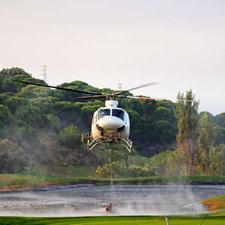 Cabopino Golf, Spain - September 12, 2011 - Bell 412 registration EC-IPM collecting water for fire fighting from a golf club lake, Cabopino Golf, Costa del Sol, Malaga Province, Andalucia, Spain, Western Europe