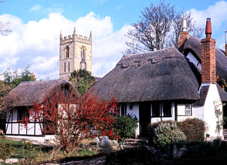 Thatched cottages with church spire to the rear, Welford on Avon, Warwickshire, England, UK, Western Europe