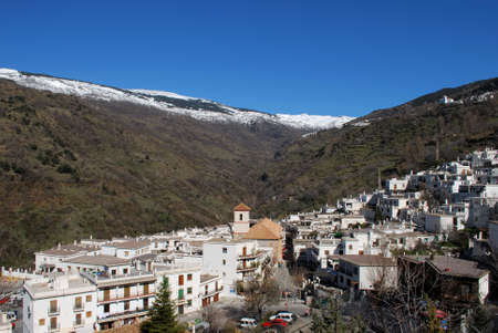 View across white village towards the snow capped mountains of the Sierra Nevada, Pampaneira, Las Alpujarras, Granada Province, Andalusia, Spain photo