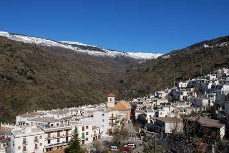 sierra snow: View across white village towards the snow capped mountains of the Sierra Nevada, Pampaneira, Las Alpujarras, Granada Province, Andalusia, Spain Stock Photo