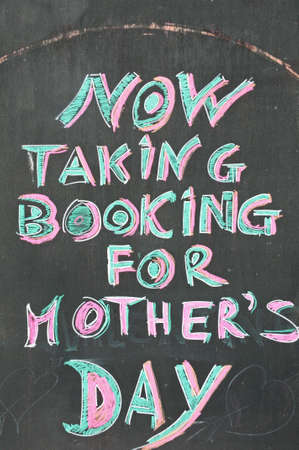 mothering: Now taking bookings for Mothers Day text written on chalkboard Stock Photo