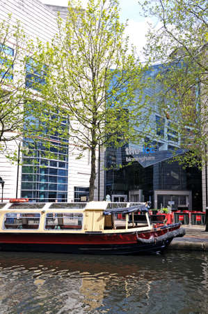 icc: Birmingham, United Kingdom - May 14, 2014 - Narrowboat converted to a canal cruiser moored outside the rear of the ICC, Brindley Place, Birmingham, West Midlands, England, UK, Western Europe