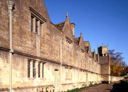 almshouse: Alms Houses  built in 1612 by Sir Baptist Hicks  with St  James Church tower to rear, Chipping Campden, Gloucestershire, England, UK, Western Europe