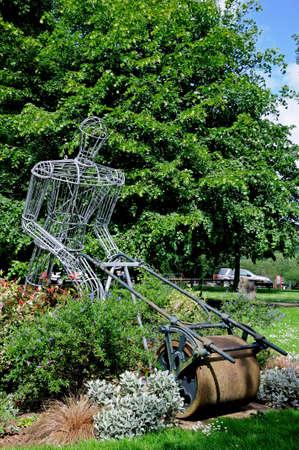 granger: Iron framed sculpture of Mr  Granger pushing a lawnmower on the grange cricket ground, Leominster, Herefordshire, England, UK, Western Europe