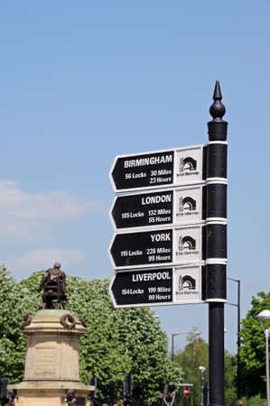 mileage: Stratford-upon-Avon, UK - May 18, 2014 - Canal mileage Signpost with the Gower memorial to the rear, Stratford-Upon-Avon, Warwickshire, England, Western Europe