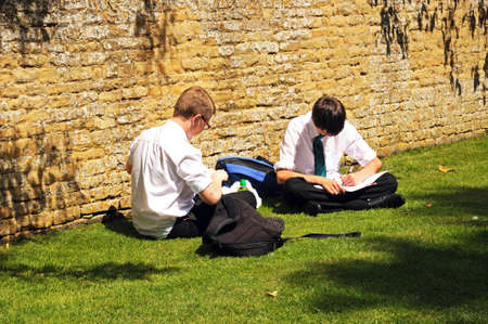 schoolwork: Bourton on the Water, UK - June 12, 2014 - Two teenage schoolboys sitting on the grass by a Cotswold stone wall doing their schoolwork, Bourton on the Water, Gloucestershire, England, UK, Western Europe  Editorial