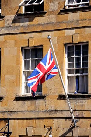 cotswold: Union Jack bandiera su un pennone collegato a un edificio in pietra del Cotswold lungo la High Street, Chipping Campden, Cotswolds, Gloucestershire, Inghilterra, Regno Unito, Europa Occidentale Archivio Fotografico