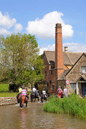 watermill: Lower Slaughter, UK - June 12, 2014 - Group of people riding horses along the River Eye with the old watermill to the rear, Lower Slaughter, Cotswolds, Gloucestershire, England, UK, Western Europe
