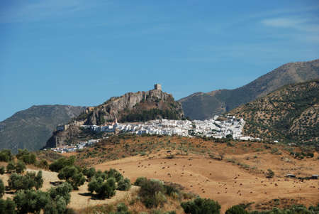 View of the town with a castle on top of the hill in Zahara de la Sierra, Spain photo