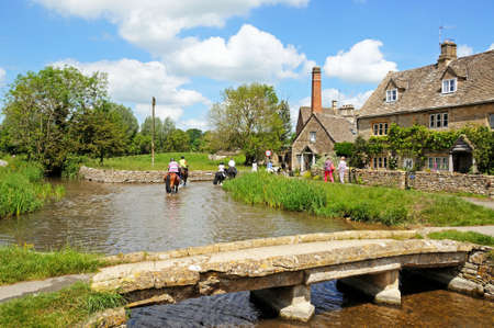 Lower Slaughter, UK - June 12, 2014 - Cotswold cottages alongside the river Eye and people riding horses along the riverbed, Lower Slaughter, Cotswolds, Gloucestershire, England, UK, Western Europe