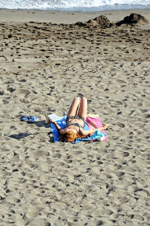 Marbella, Spain - September 26, 2011 - Woman lying on the beach reading a book, Marbella, Costa del Sol, Malaga Province, Andalucia, Spain, Western Europe