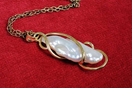 freshwater pearl: Baroque pearl pendant against a red background