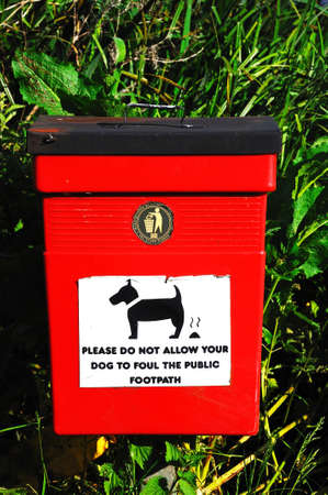 Red litter bin with a dog fouling message on the front, Barton-under-Needwood, Staffordshire, England, UK, Western Europe