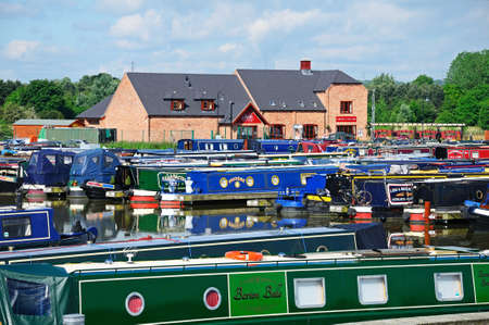 gb: BARTON-UNDER-NEEDWOOD, UK - MAY 21, 2014 - Narrowboats on their moorings in the canal basin with shops, bars and restaurants to the rear, Barton Marina, Barton-under-Needwood, Staffordshire, England, UK, Western Europe