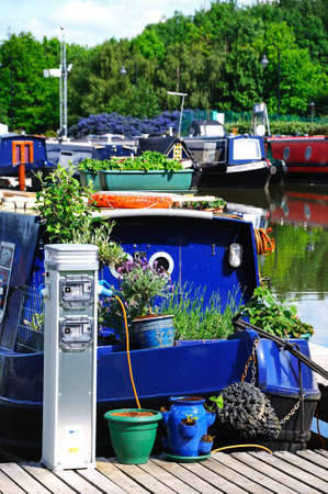 moorings: BARTON-UNDER-NEEDWOOD, UK - MAY 21, 2014 - Narrowboats on their moorings hooked up to electricity supplies in the canal basin, Barton Marina, Barton-under-Needwood, Staffordshire, England, UK, Western Europe  Editorial