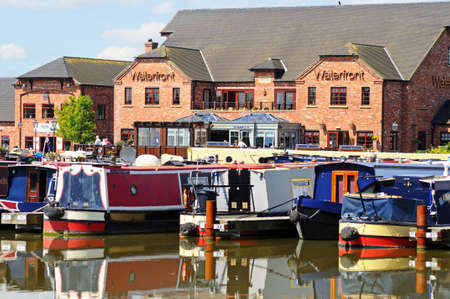 moorings: Barton-under-Needwood, UK - May 21, 2014 - Narrowboats on their moorings in the canal basin with shops, bars and restaurants to the rear, Barton Marina, Barton-under-Needwood, Staffordshire, England, UK, Western Europe