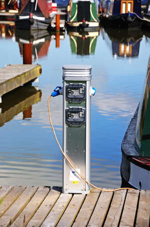 gb: Barton-under-Needwood, UK - May 21, 2014 - Metered electricity supply unit on the jetty being used by a narrowboat in the canal basin, Barton Marina, Barton-under-Needwood, Staffordshire, England, UK, Western Europe