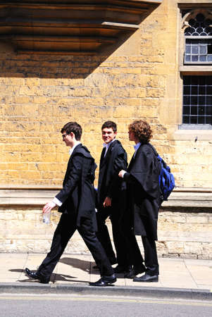 academic dress: Oxford, United Kingdom - June 17, 2014 - Students walking along the High Street wearing academic dress, Oxford, Oxfordshire, England, UK, Western Europe  Editorial
