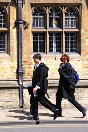 academic dress: Oxford, UK - June 17, 2014 - Students walking along the High Street wearing academic dress, Oxford, Oxfordshire, England, UK, Western Europe