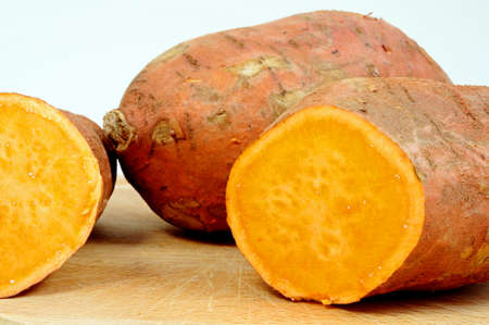 halved  half: Raw sweet potatos on a wooden board  Stock Photo