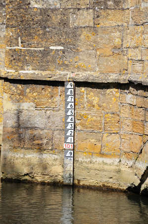 depth gauge: Medieval stone bridge over the river Windrush showing the depth marker, Burford, Oxfordshire, England, UK, Western Europe
