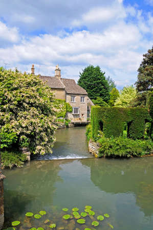 View of the weir on the river Windrush with riverside cottages to the rear, Burford, Oxfordshire, England, UK, Western Europe