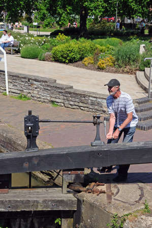 canal lock: Stratford-upon-Avon, UK - May 18, 2014 - Man opening canal lock gate, Stratford-Upon-Avon, Warwickshire, England, United Kingdom, Western Europe