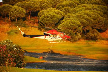 西ヨーロッパ、スペイン、アンダルシア州マラガ州コスタ ・ デル ・ ソル Cabopino ゴルフ ゴルフコース湖から消火のための水を収集 Cabopoino、スペイン - 2011 年 9 月 12 日 - 鐘 412 ヘリコプター登録 N167EH