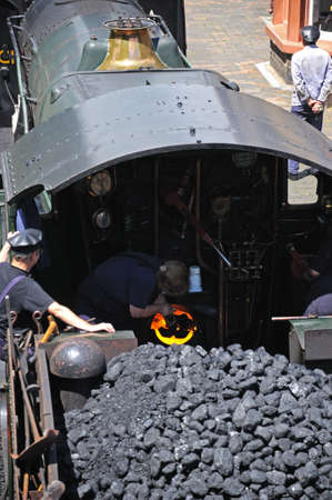 footplate: Arley, UK - July 10, 2014 - Steam Locomotive 7800 Class 4-6-0 Erlestoke Manor number 7812 with train worker stoking the boiler, Severn Valley Railway, Arley, Worcestershire, England, UK, Western Europe