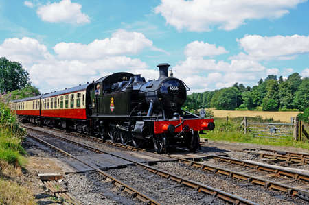 br: Arley, UK - July 10, 2014 - Small Prairie Tank Locomotive 4500 Class 2-6-2T number 4566 in British Railways Black pulling carriages in BR Crimson Cream livery, Severn Valley Railway, Arley, Worcestershire, England, UK, Western Europe
