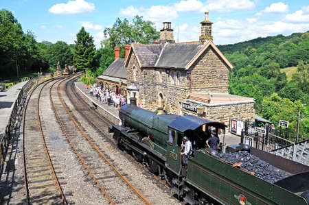 Highley, UK - July 10, 2014 - Steam Locomotive 7800 Class 4-6-0 Erlestoke Manor number 7812 in Great Western Railways green with the late British Rail Crest approaching the railway station platform, Highley, Worcestershire, England, UK, Western Europe