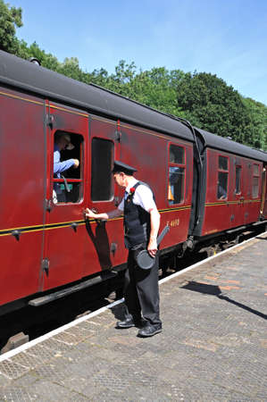 disembark: Highley, UK - July 10, 2014 - Porters alongside the LMS British Rail Maroon railway carriages ready to help passengers disembark, Highley, Worcestershire, England, UK, Western Europe