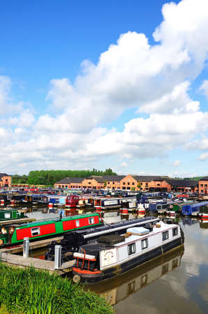 hooked up: Barton-under-Needwood, UK - May 21, 2014 - Narrowboats on their moorings hooked up to electricity supplies in the canal basin with bars, shops and restaurants to the rear, Barton Marina, Barton-under-Needwood, Staffordshire, England, UK, Western Europe.