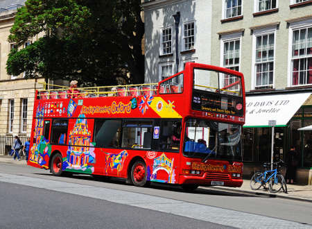 Oxford, UK - June 17, 2014 - Red open topped Oxford tour bus along High Street, Oxford, Oxfordshire, England, UK, Western Europe.