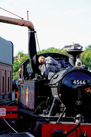 refilling: Bridgnorth, UK July 10, 2014 - Engineering re-filling the Small Prairie Tank Locomotive 4500 Class 2-6-2T number 4566 with fresh water from the water crane, Bridgnorth, Shropshire, England, UK, Western Europe. Editorial
