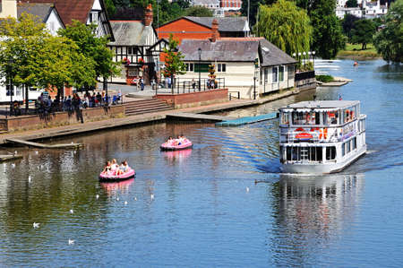 Chester, UK - July 22, 2014 - River ferry and pedalos on the River Dee, Chester, Cheshire, England, UK, Western Europe.