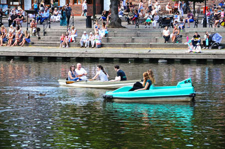 Chester, UK - July 22, 2014 - People enjoying sitting on the River Dee embankment with a pedalo and rowing boat in the foreground, Chester, Cheshire, England, UK, Western Europe.