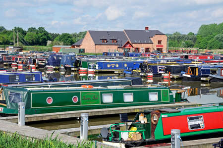 moorings: Barton-under-Needwood, UK - May 21, 2014 - Narrowboats on their moorings in the canal basin with bars, shops and restaurants to the rear, Barton Marina, Barton-under-Needwood, Staffordshire, England, UK, Western Europe.