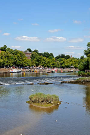 Chester, UK - July 22, 2014 - View of the weir along the River Dee with buildings to the rear, Chester, Cheshire, England, UK, Western Europe.