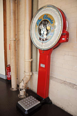 operated: Derby, United Kingdom - July 17, 2014 - Classic WSG public coin operated weighing scales in red, Derby, Derbyshire, England, UK, Western Europe.
